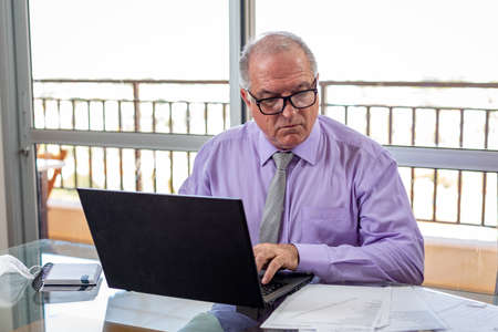 Sir typing on the notebook, working on the home office system in times of pandemic by the Corona virus. Mister works at home wearing a shirt and tie with his mask resting beside