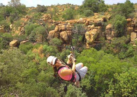 fila di persone: Lady scorrevole su una linea di zip in una gola in Sud Africa