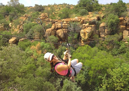 Lady sliding on a zip line across a gorge in South Africa photo
