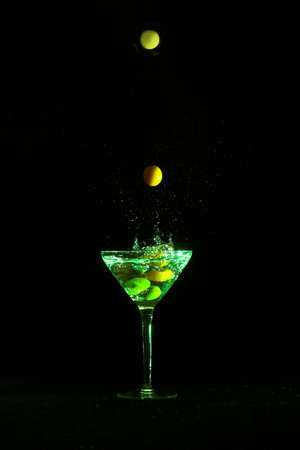 Olives dropping into martini glass, stop motion photo