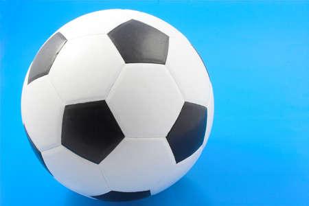 Balón de fútbol y sobre fondo azul