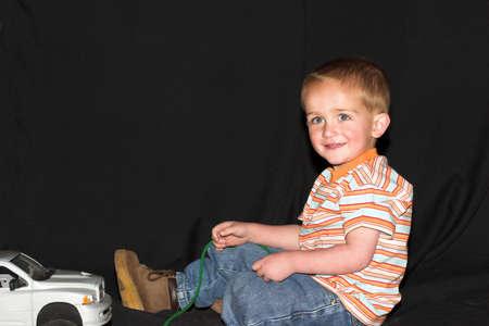 Boy jugando con camiones de juguete  Foto de archivo - 505349