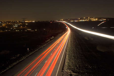 Highway at night between two cities photo