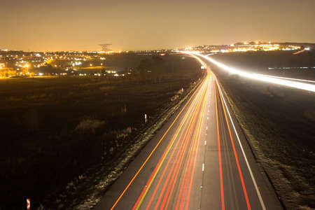 zooming: Night scene with city background over busy highway