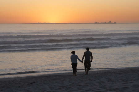 as: Couple walking on beach with sunset and ship as background