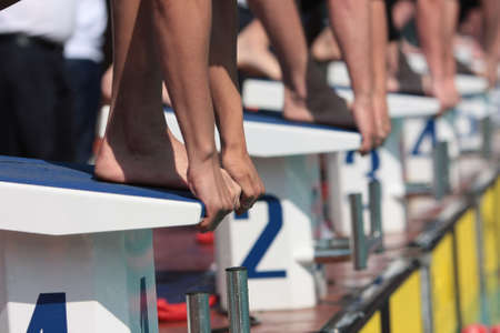 begin: Swimmers on the starting block with only hands and feet visable