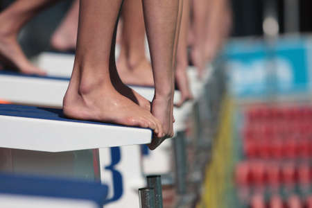 Divers on starting block ready to swim in gala, only hands and feet visable