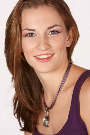 Young model with big smile, purple top and long brown hair photo
