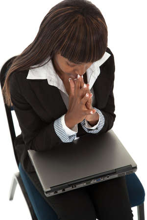 Young black female praying with laptop on legs photo