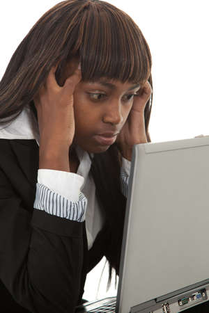 Young black female professinal with hands in hair over laptop photo