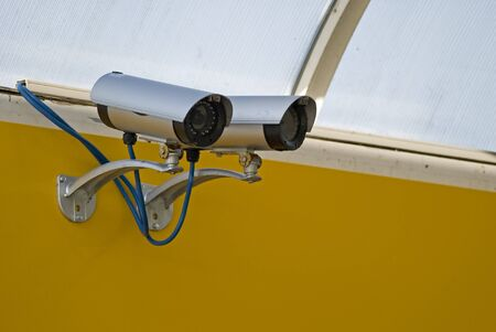 Security camera mounted on a yelow wall Stock Photo - 4038170