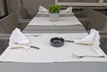 Restaurant table setting with flower and ashtray. photo