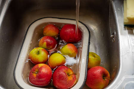 Apples in an enamel bowl under the flow water from tap in the sink Reklamní fotografie - 124815721
