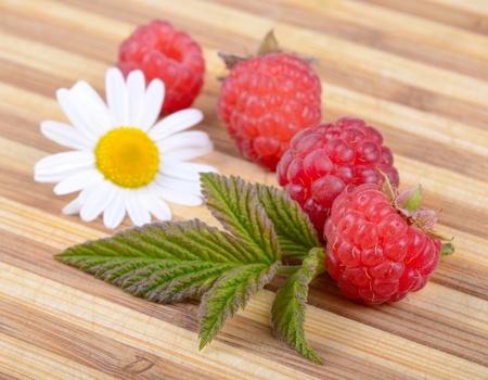 hardboard: Fresh Ripe Raspberries with Leaf and White Camomile Flower on Old Wooden Hardboard