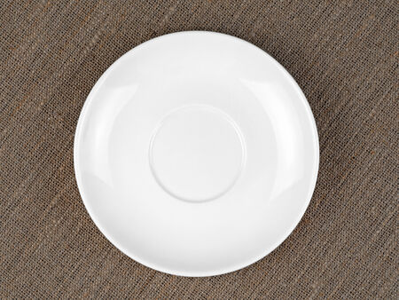 bagging: Single Empty White Plate on Coarse Fabric or Bagging Background