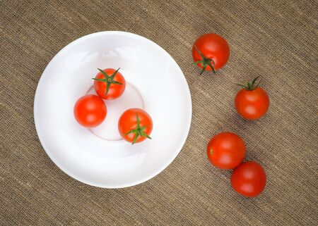 bagging: Ripe Fresh Cherry Tomatoes on White Plate on Coarse Fabric or Bagging Background