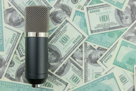 Toned microphone on dollar bills background