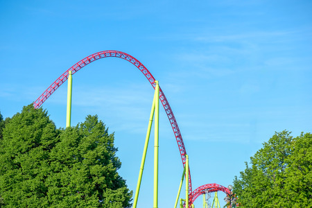 A rollercoaster ride against a blue sky with trees.