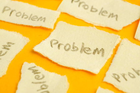 The concept of many unsolved problems or depression. Ragged sticker with the word problem on a yellow background. Close up.