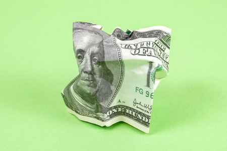 Crumpled hundred dollar bills of usa on a green background. The concept of currency crisis. Close up.