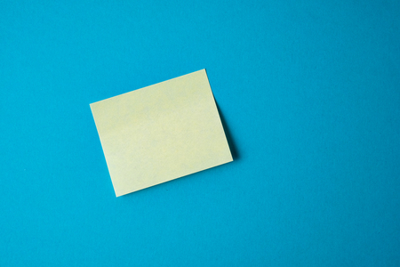 Yellow paper sticker on blue background. Close up.