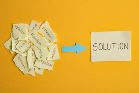 The concept of the found solution from a set of unsolved problems. Ripped stickers with the word problem with a sticker that says solution on a yellow background. 写真素材