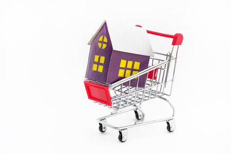 The concept of buying a private house or apartment. Loan for housing. Metal cart on a white background with a toy house. Close up. Banque d'images - 113489453
