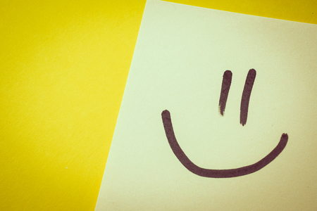 The concept of happiness from office work. Yellowish sticker with a face of joy on a yellow background. Toned. Stock fotó
