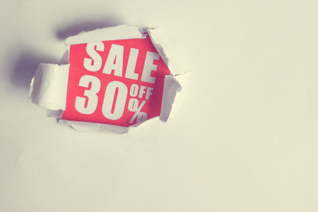 The concept of sales in the form of discounts 30. The inscription on the red paper coming out of the white paper. Toned. Imagens - 118726325
