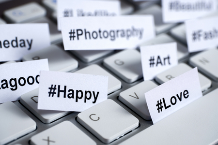 Popular hashtags printed on white paper inserted into the keyboard. Stock fotó
