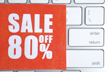 """Red paper label with an inscription """"sale off 80%"""" on a white keyboard."""