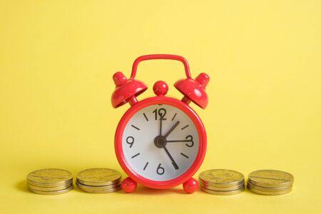 Das Konzept, in einer Krise Geld zu sparen. Eine rote Vintage-Uhr steht auf einem Stapel Münzen auf gelbem Grund.