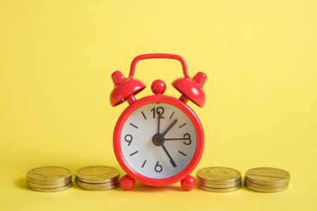 The concept of saving money in a crisis. A red vintage clock stands on a stack of coins on a yellow background.
