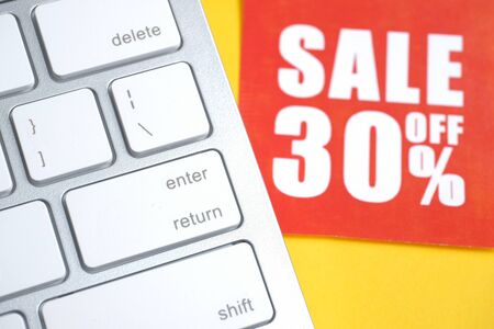 "Red paper label with an inscription ""sale off 30%"" on a white keyboard on a yellow background."