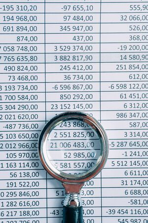 Magnifier lies on paper with totals. Concept financial reports. Toned. Copy space.