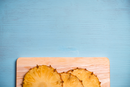 Ripe pineapple pieces on board and blue wooden table. Top view. Copy space. Center down. 스톡 콘텐츠