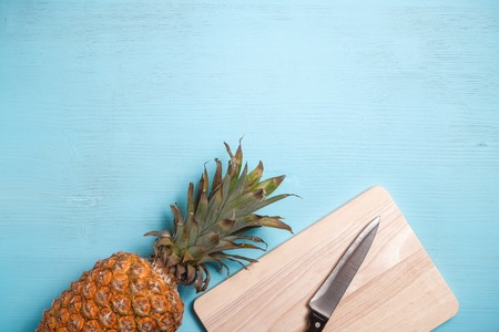 Ripe pineapple next to a wooden board and a knife on a blue wooden table. Copy space. top view.
