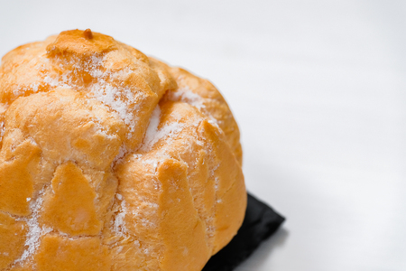 Sweet bun with cream on a shale dishes and wooden background. Close up.