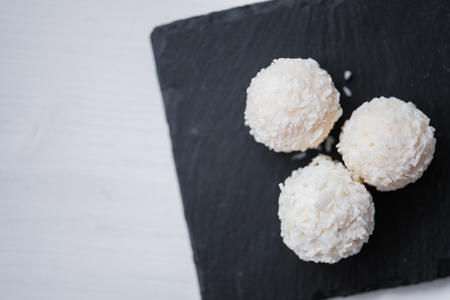 White coconut candy balls in plate shale dishes on rustic wooden background. Top view. Copy space. Right side.