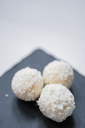White coconut candy balls in plate shale dishes on rustic wooden background. Top view. Copy space.