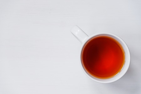 Cup of tea on white wooden table. Top view. Copy space.