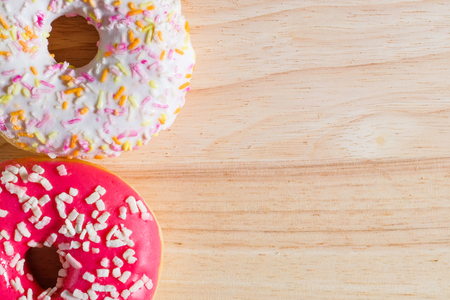 White and pink glazed donuts on wooden background. Top view. Copy Space.