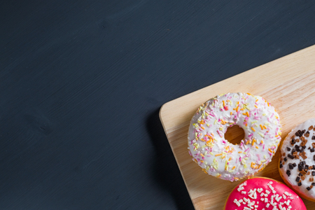 White, pink and brown glazed donuts in right side on black wooden background. Top view. Copy space.