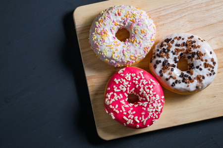 White, pink and brown glazed donuts on black wooden background. Top view.