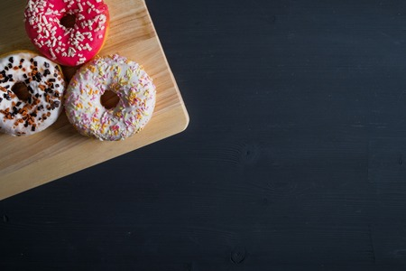 White, pink and brown glazed donuts in left side on black wooden background. Top view. Copy space.