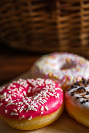 White, pink and brown glazed donuts on wooden background and near rattan basket . Close up. Vertical. Stock Photo