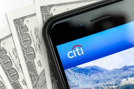 RUSSIA, ST.PETERSBURG, April 4, 2019: Logo of the bank Citigroup Inc in the smartphone lying on one hundred dollar bills. Editorial