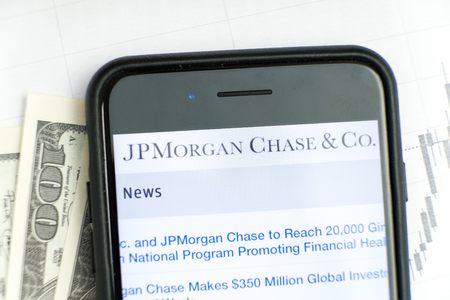 RUSSIA, ST.PETERSBURG, April 4, 2019: site with Logo of the bank J.P.Morgan Chase Co in the smartphone lying on paper with charts and one hundred dollar bills.