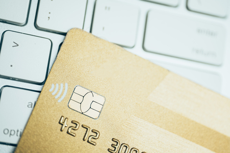 The concept of online shopping. Golden credit card on a white keyboard. Close up.