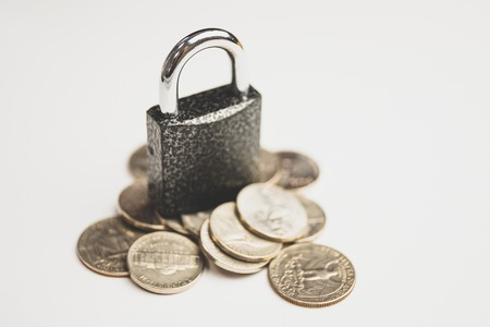 Concept of protection of cash savings. The lock on the coins and white background. Close up.